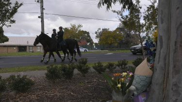 Police on horseback pass the crime scene on Wednesday afternoon.