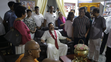 Mahinda Rajapaksa (centre) talks with supporters at a Buddhist temple in Colombo.