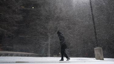 Seorang wanita berjalan melewati salju yang turun di San Antonio.