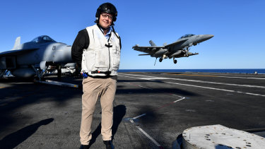 Australian Prime Minister Scott Morrison is seen on the flight deck as a EA-18G Growler lands on the USS Ronald Reagan, off the coast of Queensland.