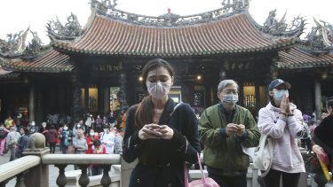 People wear face masks to protect against the spread of the coronavirus as they pray in Taipei, Taiwan.