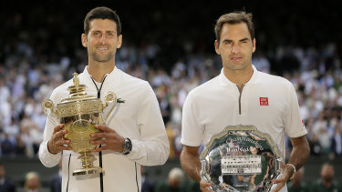 Novak Djokovic and Roger Federer  with the trophies after the Serb's win in the 2019 Wimbledon final.