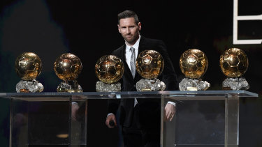 World's best: Lionel Messi poses onstage after winning his sixth Ballon D'Or on Monday.