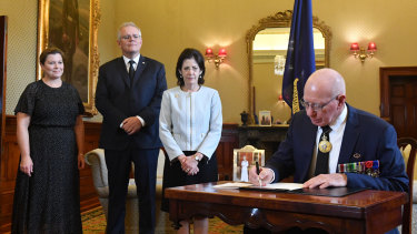 Governor-General David Hurley signs a condolence book as his wife Linda Hurley, Prime Minister Scott Morrison and his wife Jenny Morrison watch on.