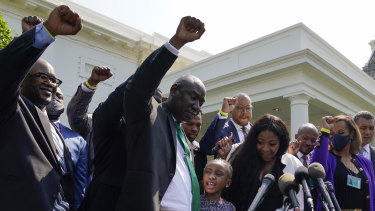 Lawyer Benjamin Crump, front centre, along with Gianna Floyd, daughter of George Floyd, and her mother Roxie Washington, and others talk with reporters after meeting with President Joe Biden at the White House.