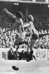 Collingwood's Rene Kink and North's Daryl Sutton are eluded by the ball.