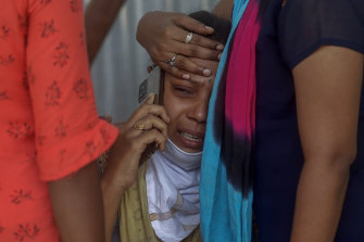 Relatives of a person who died of COVID-19 mourn outside a field hospital in Mumbai, India.