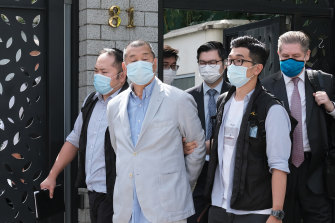 Jimmy Lai, chairman of Next Digital is led away from his residence by law enforcement officials in Hong Kong on Monday.