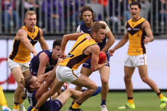 Hawthorn's Harry Morrison looks to break free from a Nat Fyfe tackle.