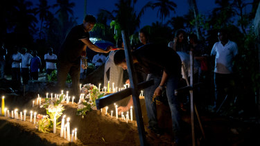 Relatives light candles after the burial of three victims of the same family, who died at Easter Sunday bomb blast at St. Sebastian Church in Negombo, Sri Lanka.
