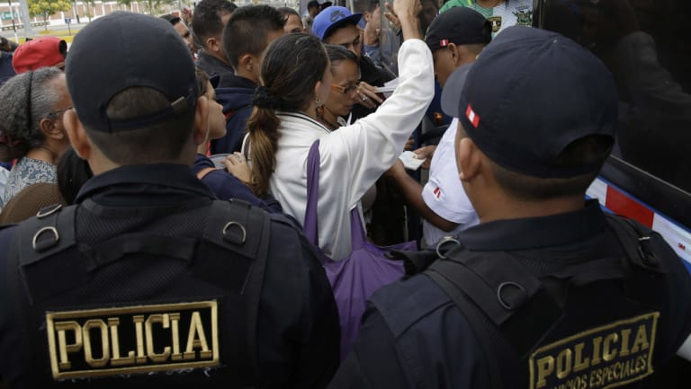 Venezuelan migrant try to get a ride in a bus to continue their travel in Peru on Saturday.