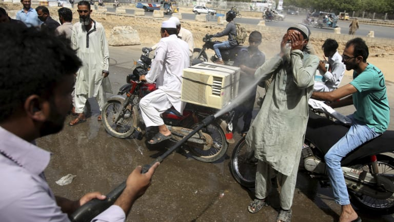 People volunteer to be sprayed in Karachi, Pakistan, as the mercury climbed well into the 40s this month.