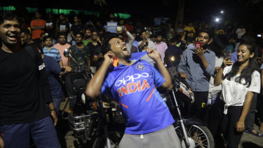 Fans celebrate the victory in Mumbai.