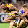 Chris Masten (left) of the Eagles is tackled by Mitch Robinson of the Lions