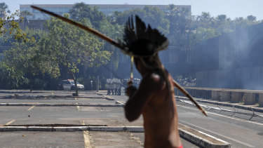 An Indigenous protester aims his bow an arrow at police outside Congress in Brasilia, Brazil.