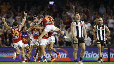 Brisbane players celebrate an after-the-siren goal by Zac Bailey.