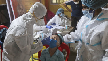 Health workers collect a swab from a boy in Mumbai to test him for COVID-19.