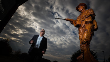Bill Cantwell with the sculpture in Greensborough War Memorial Park of himself as a Vietnam War soldier.