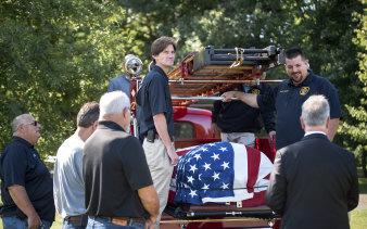Joe Heller's coffin is carried on the Essex Fire Department's 1941 Mack firetruck that Heller helped restore, in Connecticut.