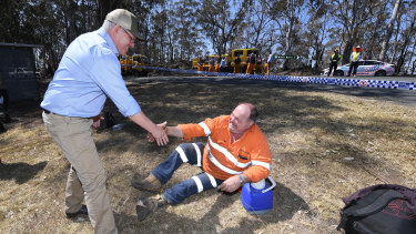 Australian Prime Minister Scott Morrison shakes hands with an emergency services worker taking a rest during a visit to the bushfire affected area of Binna Burra.