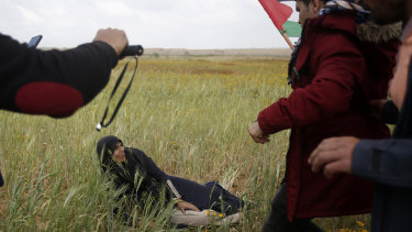 Palestinian protesters try to evacuate a wounded woman during clashes with Israeli troops along the Gaza Strip border.