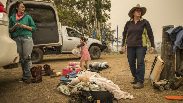 Dungay cattle farmers (from left) Lisa Lincoln with Alice Lincoln and grandmother Sue Clarke, pack their vehicle ahead of worsening bushfire conditions on Tuesday.