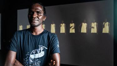 Artist Gutingarra Yunupingu, winner of the Telstra Multimedia Award in front of his piece, Gurrutu'mi Mala - My connections.