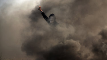 A Palestinian protester flashes the V sign during a protest near the Gaza Strip border with Israel, in eastern Gaza City, on Saturday.