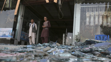 Afghans stand near a damaged shop after the explosion.