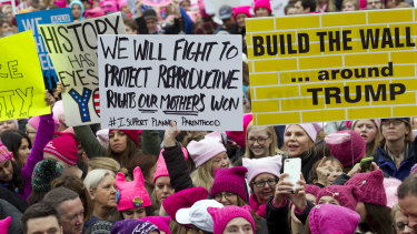 Women with bright pink hats and signs make their voices heard on the first full day of Donald Trump's presidency, Saturday, January 21, 2017.