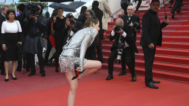Actress Kristen Stewart pictured removing her Christian Louboutin shoes on the red carpet at the Cannes film festival.