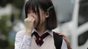 A woman sheds tears as she visits a makeshift memorial honouring the victims of Thursday's fire at the Kyoto Animation Studio.