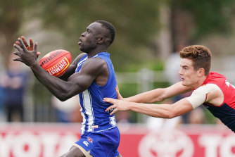 The Kangaroos' Majak Daw marks ahead of Bayley Fritsch of the Demons on Friday.