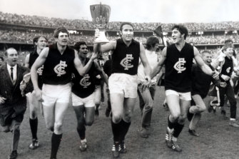 Carlton captain John Nicholls holds the premiership cup as Carlton laps the MCG.