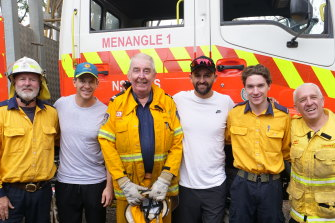 Tim Paine and Nathan Lyon pose for a photo with RFS firefighters in the Southern Highlands on Wednesday.