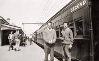 Train enthusiasts even then, Tom Clark, left, and his twin brother Kevin in the 1960s next to a steam-hauled train they travelled on.