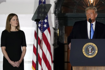 Amy Coney Barrett listens to US President Donald Trump at her Supreme Court swearing in ceremony at the White House on Monday night (Tuesday AEDT).