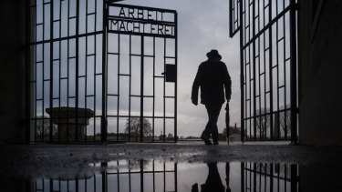 A man walks through the gate of the Sachsenhausen Nazi death camp with the phrase 'Arbeit macht frei' (work sets you free) in Oranienburg, Germany, on International Holocaust Remembrance Day.