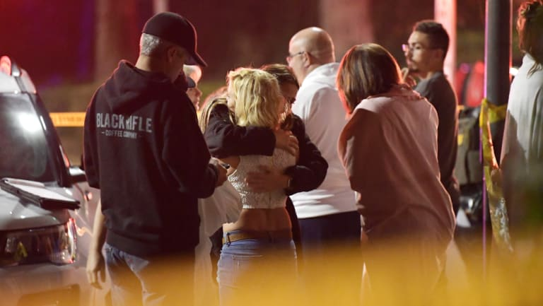 "People comfort each other as they stand near the scene in Thousand Oaks, California, where a gunman opened fire inside a country dance bar crowded with hundreds of people on ""college night""."