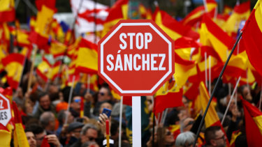Demonstrators hold banners and Spanish flags during a protest in Madrid, Spain, on Sunday.