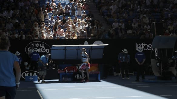 Petra Kvitova waits as officials close the roof on Rod Laver Arena.