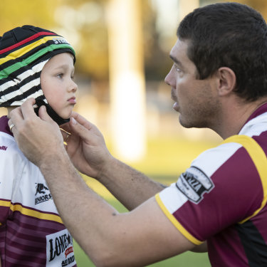 Father Sean Buchanan adjusts the headgear on his six-year-old son Beau, who plays for the Glenmore Park Brumbies in the Penrith Junior Rugby League.