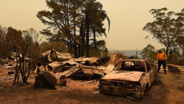 RFS assessment officer Adam Small inspects a home burnt out during the Green Wattle Creek Fire South West of Sydney.