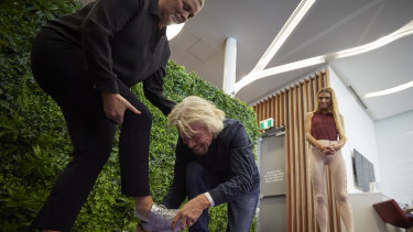 Ever the gentleman, Sir Richard Branson helping Samantha Armytage with her shoes in the Virgin Lounge on Thursday.