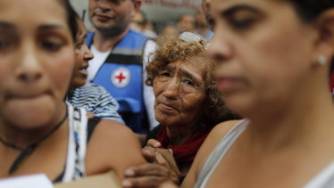 People wait to be given empty water containers and water purification pills during the first aid shipment from the International Red Cross in Caracas, Venezuela.