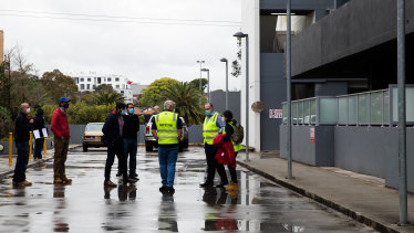 Building inspectors gather outside the Charles Street development on Wednesday afternoon.