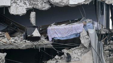 Una cama cuelga del edificio derrumbado.