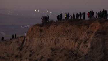 Members of the public and journalists stand on a hill to watch an emergency landing of the Air Canada flight in Madrid.