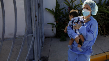 Nurse Claudia Rivas, cradling her son, arrives to receive a dose of the Sputnik V COVID-19 vaccine, as part of a vaccination campaign in Tegucigalpa, Honduras.