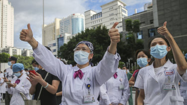 Medical workers from a provincial hospital in Fuzhou give thumbs-up to their colleagues leaving to help with an outbreak of COVID-19 in Putian.
